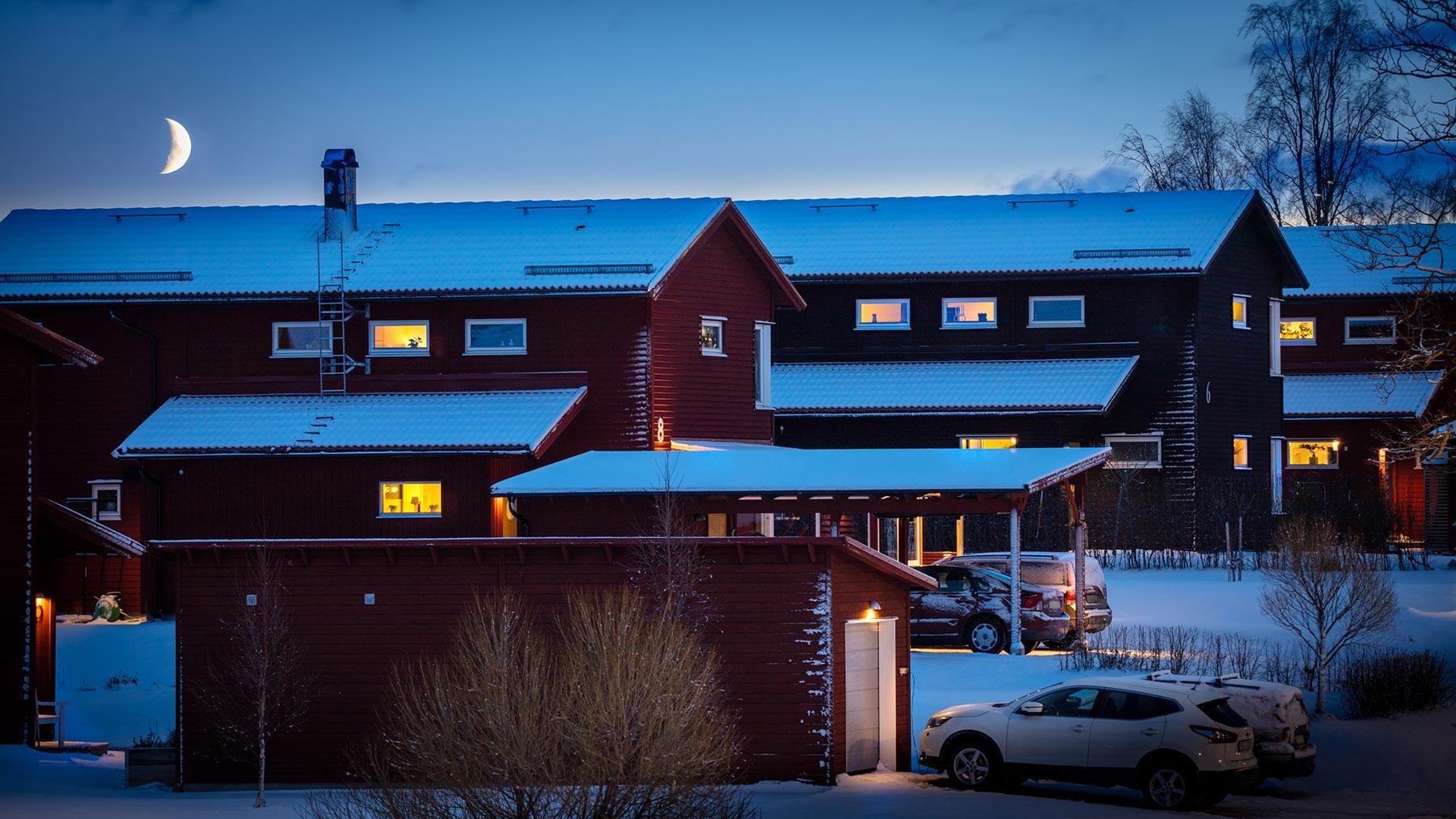 Illustrativ bild som föreställer ett bostadsområde. Månen lyser över taken och inomhusbelysnigen lyser upp fönstren på de röda husen. Nysnö ligger på marken och bilar står parkerade utanför husen.