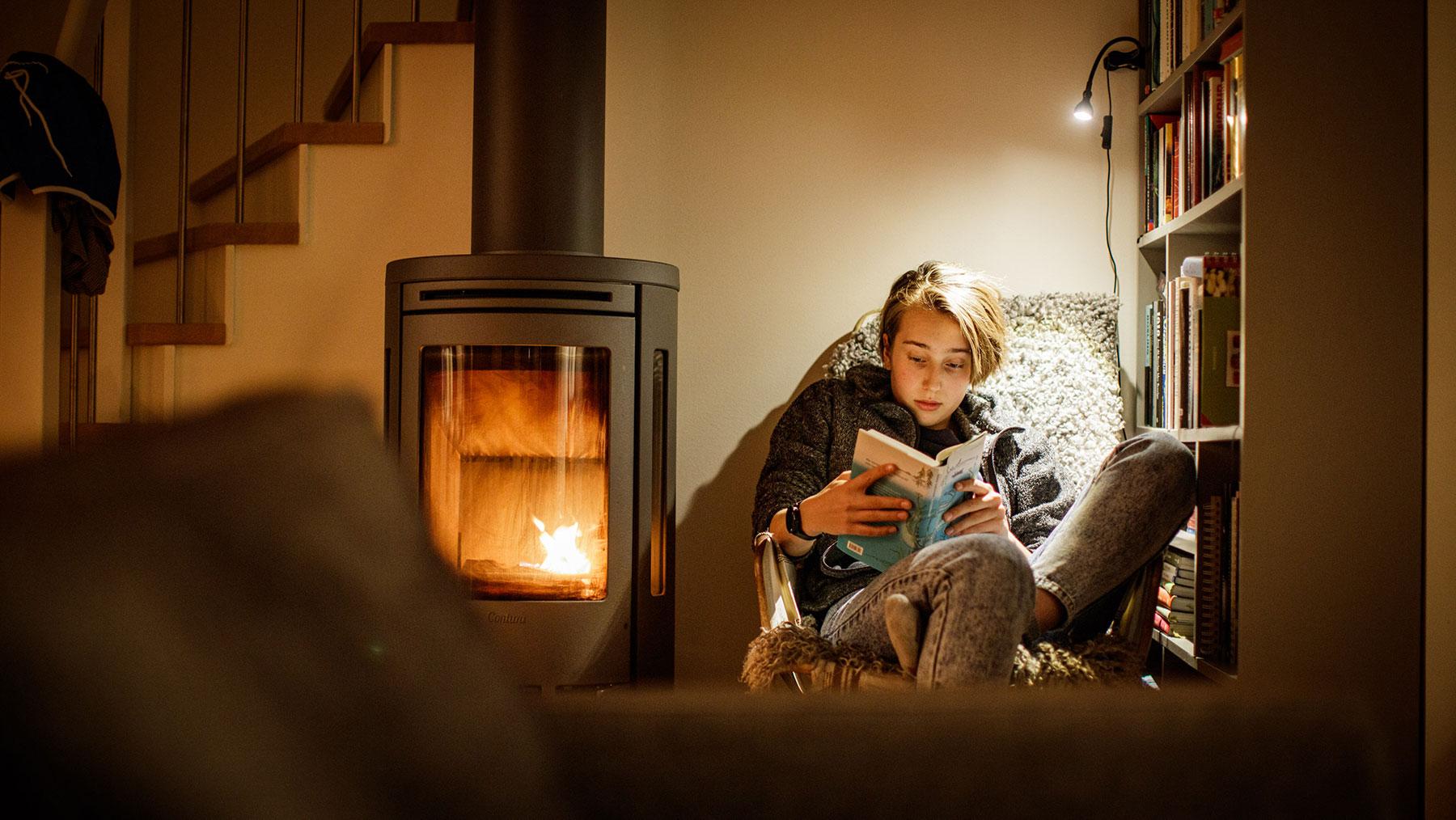 En person som läser en bok bredvid en tänd kamin