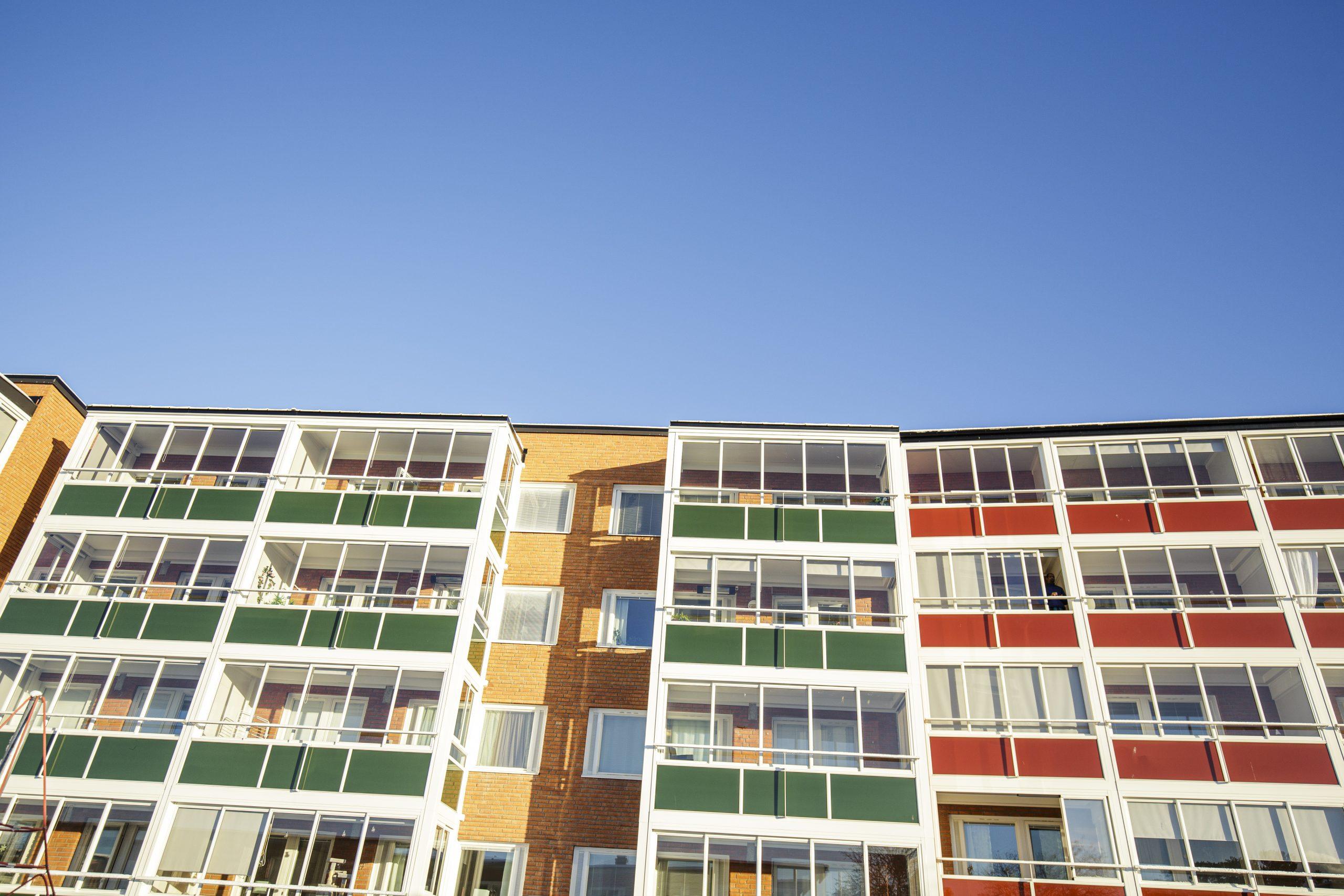 Lägenhetshus med inglasade gröna och röda balkonger, ses nedifrån. Det är soligt och ovanför husen syns en blå himmel.