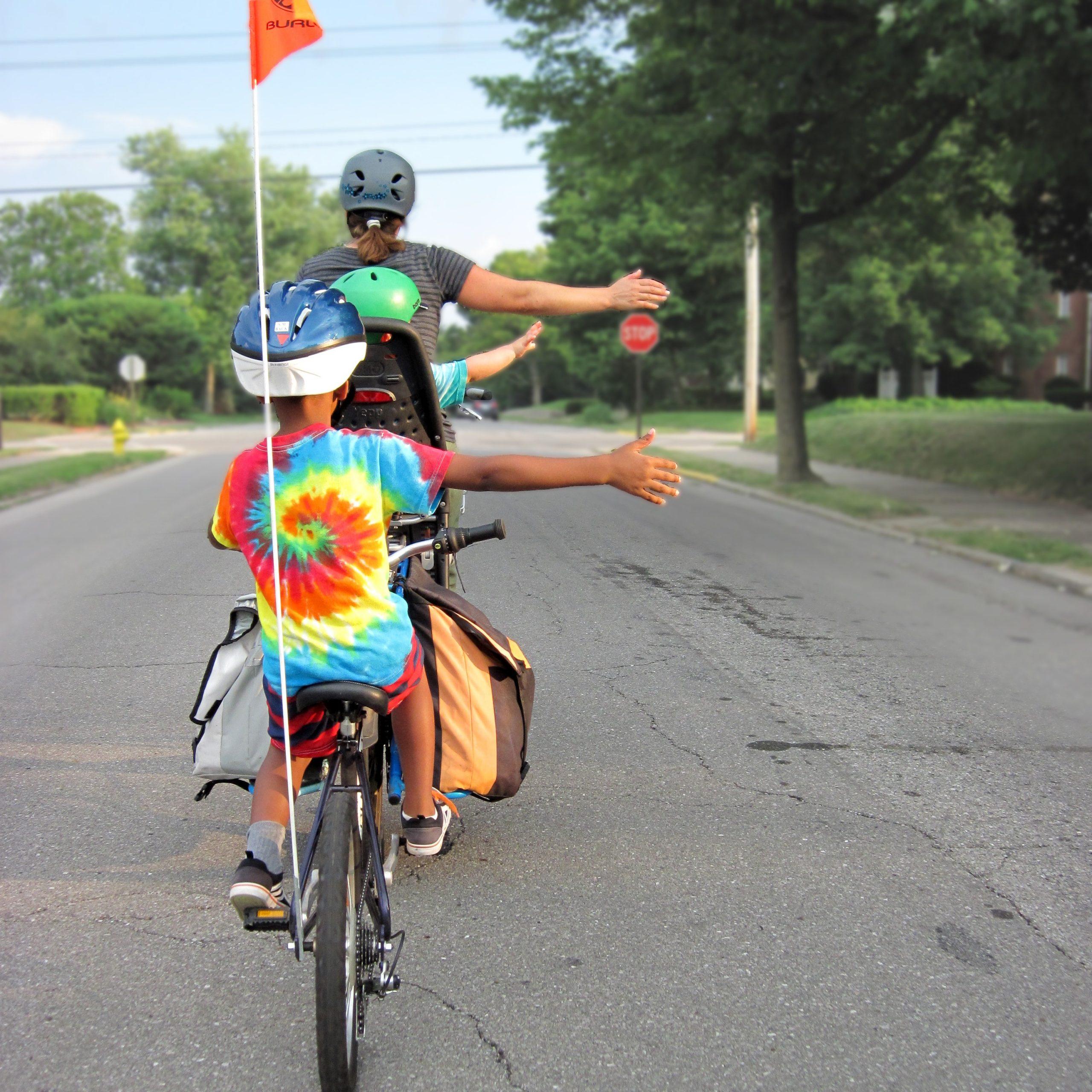 Ryggen på två barn och en vuxen syns. De cyklar på en asfalterad väg och håller ut höger armen åt sidan för att visa att de ska svänga. Barnet längst bak bär en färgglad T-shirt och en blå cykelhjälm.