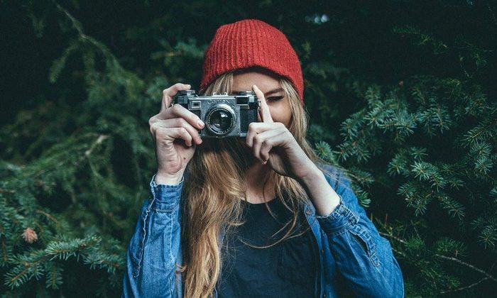 Dekorativ bild, person tittar genom kamera med grön skog i bakgrunden.